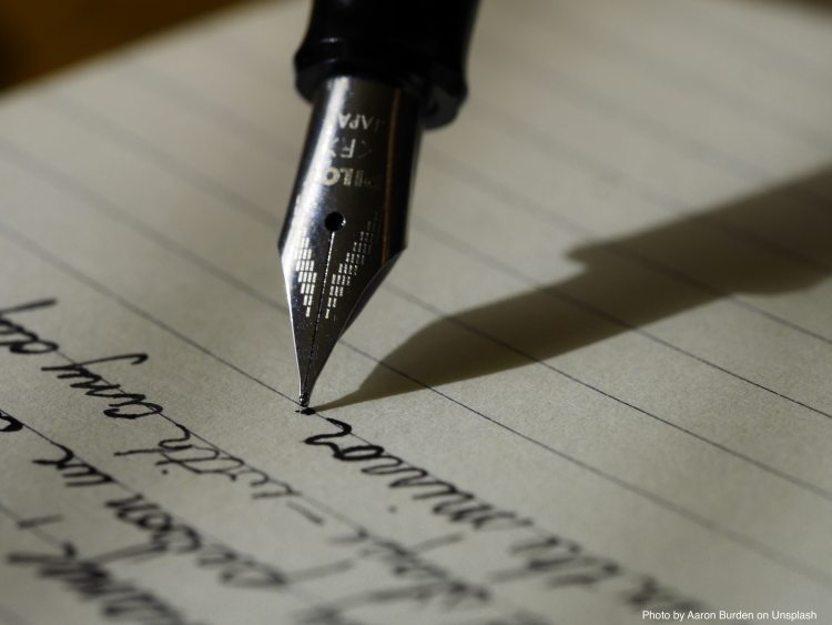 Image of an ink pen poised over a paper with cursive writing. It symbolises creativity in writing.